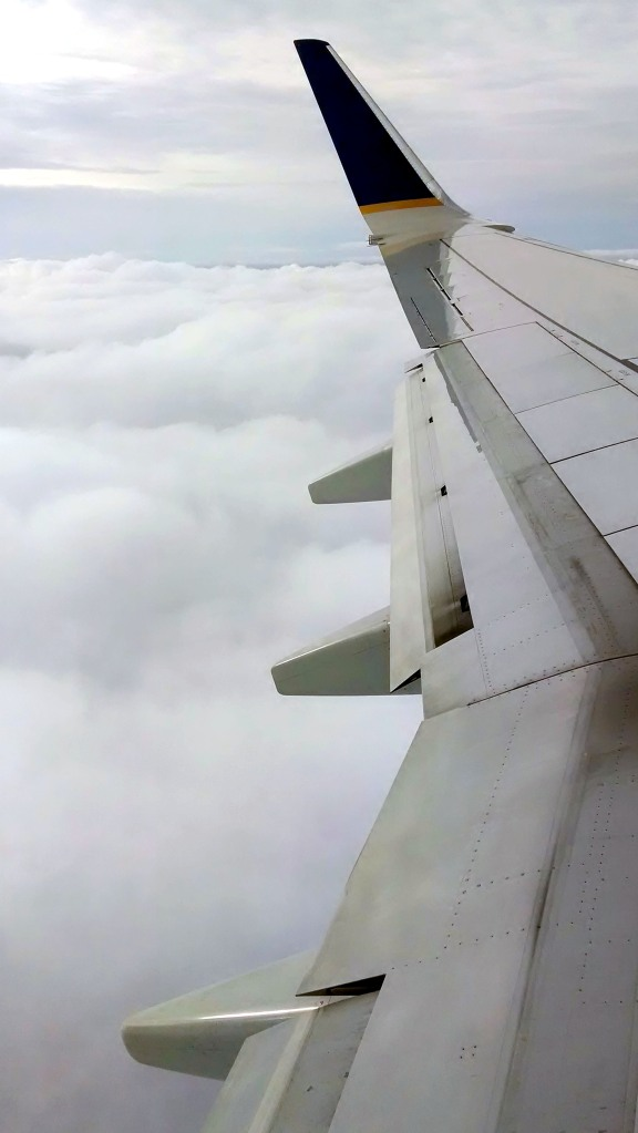 flying airplane wing through the clouds