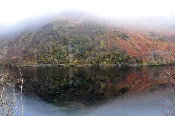 hillside reflected in water