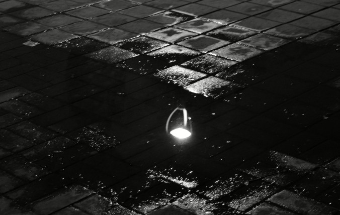 street light reflected in puddle, black and white