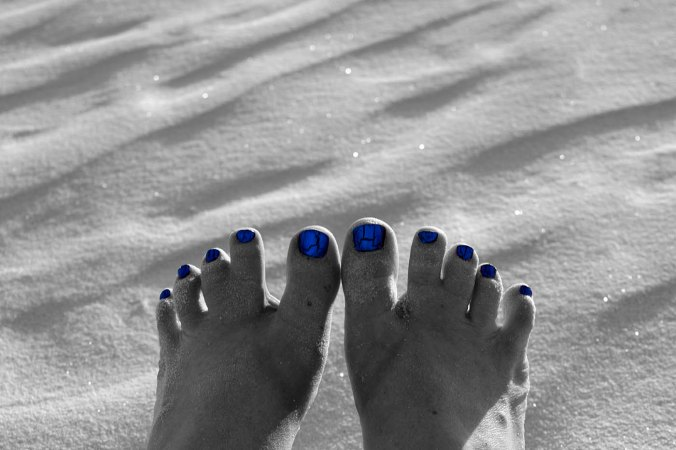 black and white feet with blue toes on sand
